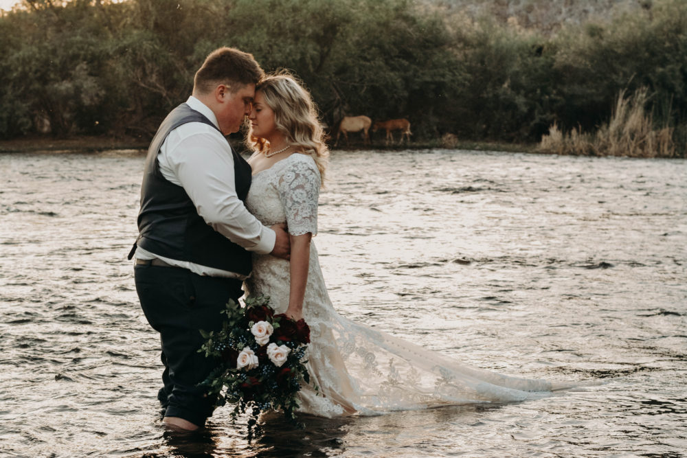 bride in sheath lace wedding gown with sleeves standing in lake with groom