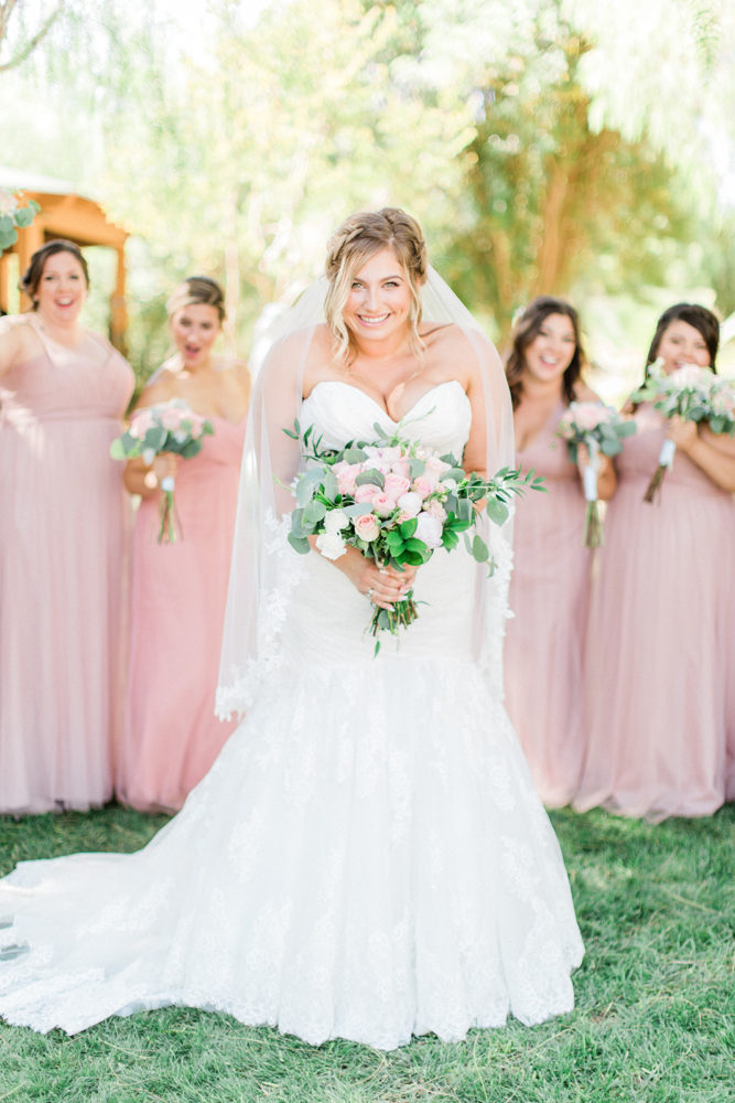 curvy bride in plus size mermaid wedding gown with bridesmaids in the background.