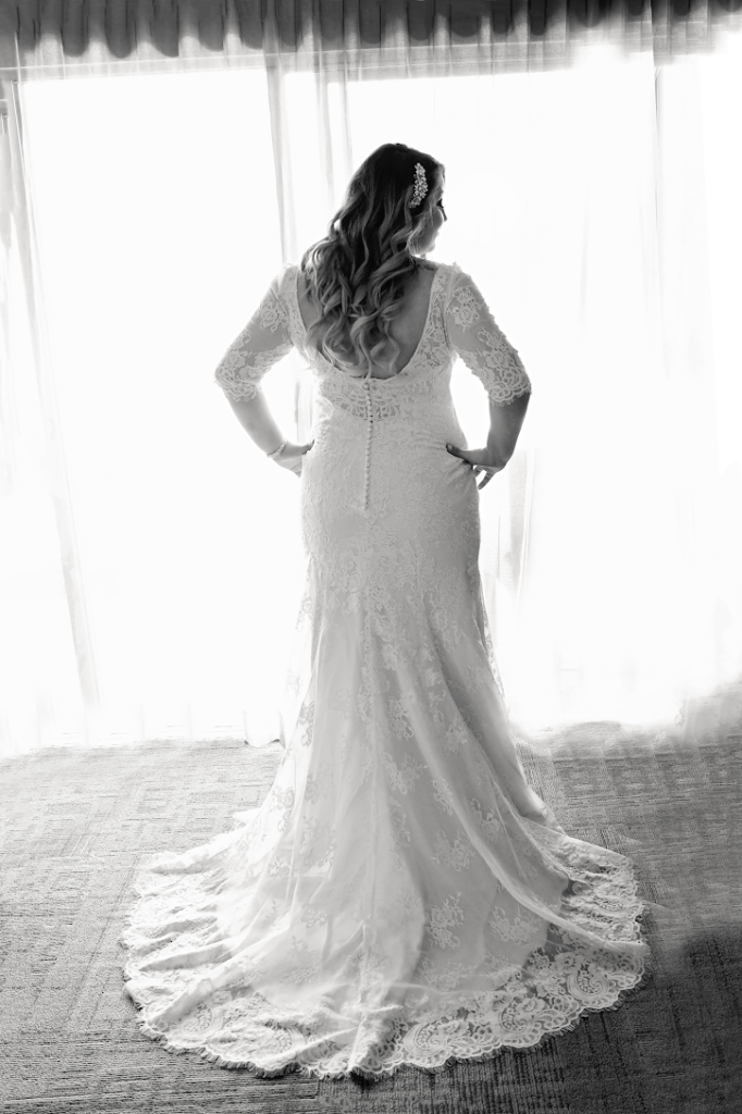 curvy bride in plus size lace wedding gown with sleeves