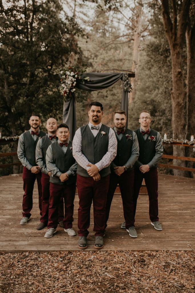Groomsmen in vests and maroon pants.
