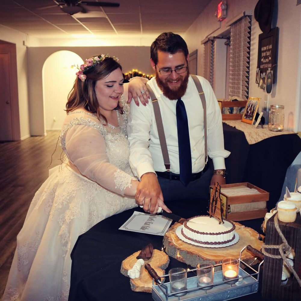 plus size bride cutting the cake