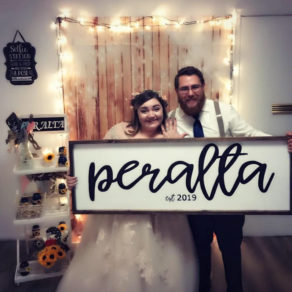 newlyweds holding sign