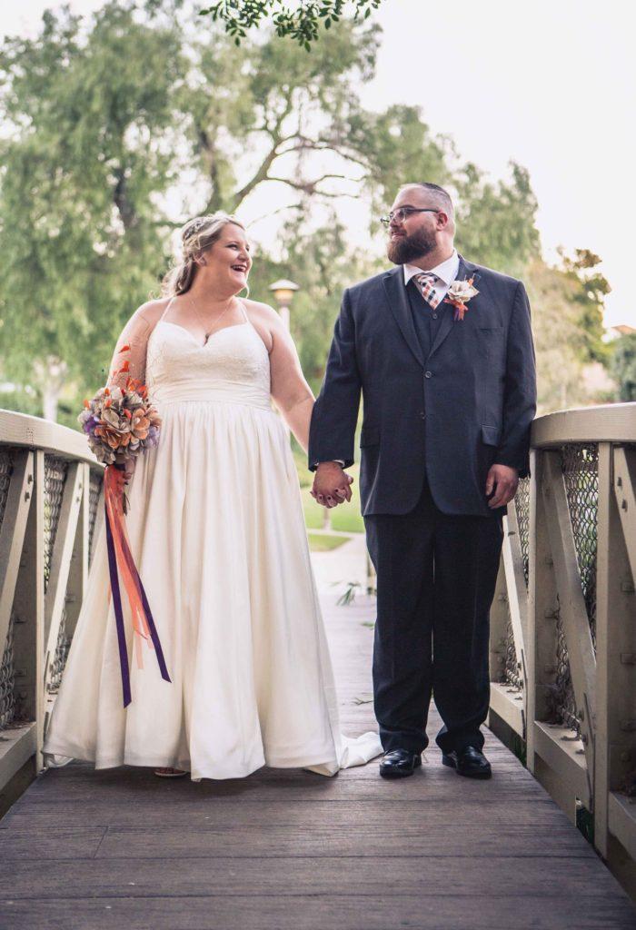 plus size wedding dress lace top and taffeta ballgown standing on a bridge