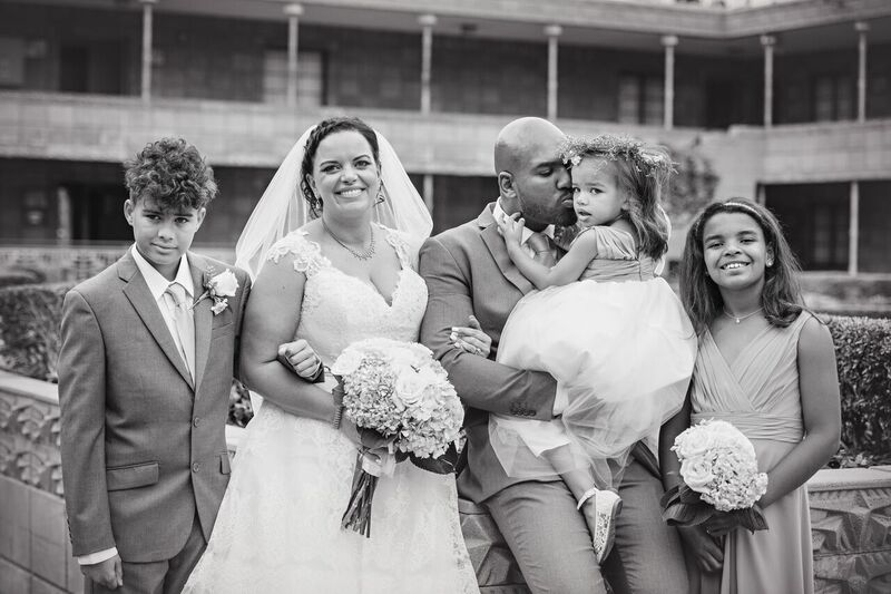 cute candid of plus size bride with groom giving daughter a peck on the cheek