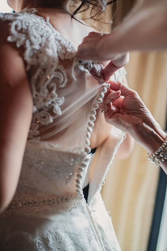 curvy bride in  show stopping a line wedding dress getting her buttons done by mom