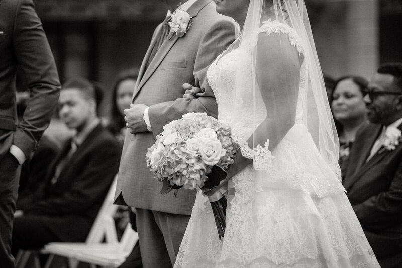 black and white photo of curvy bride in  show stopping a line wedding dress walking down the aisle