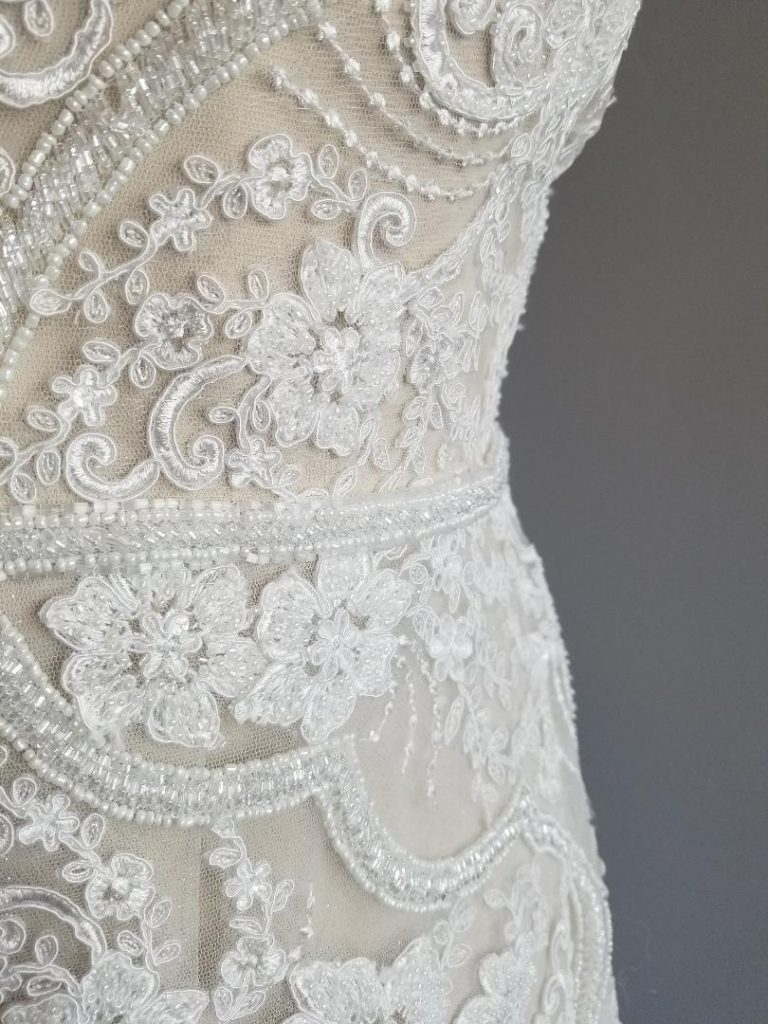 close up of plus size wedding dress beaded and lace sheath