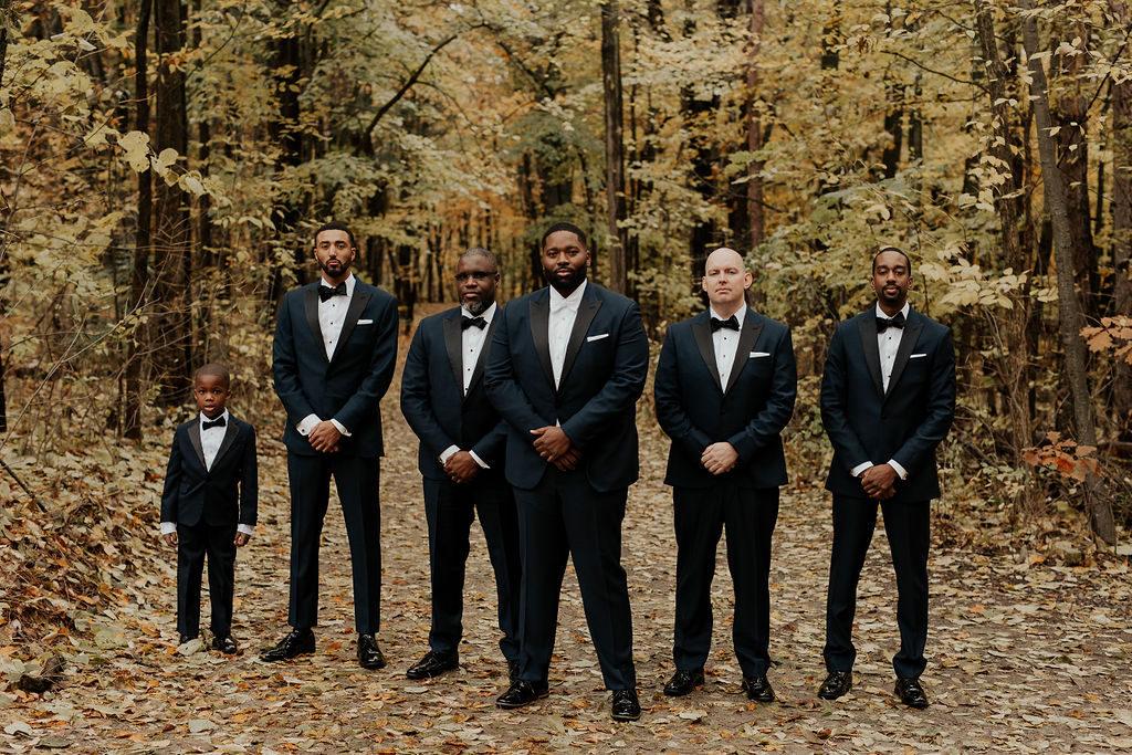 groomsmen standing in the woods