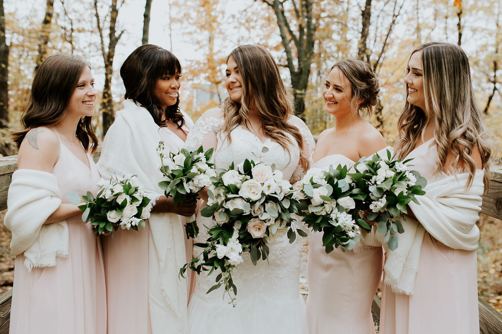 Bridesmaids wore blush pink with ivory wraps.