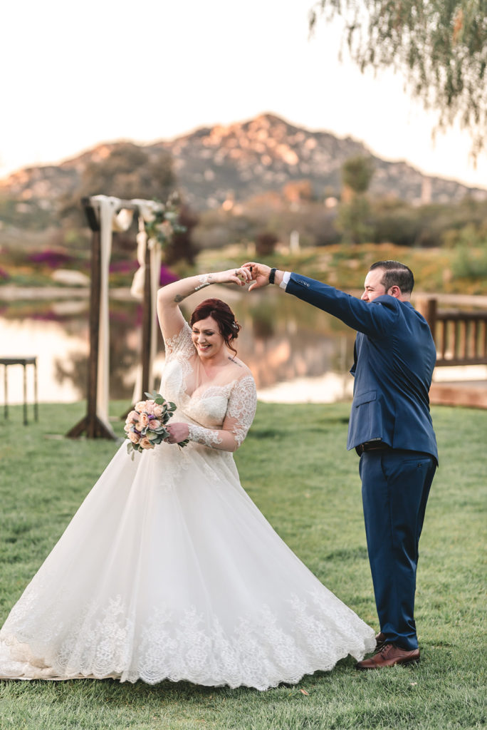newlyweds twirling on the lawn by a lake