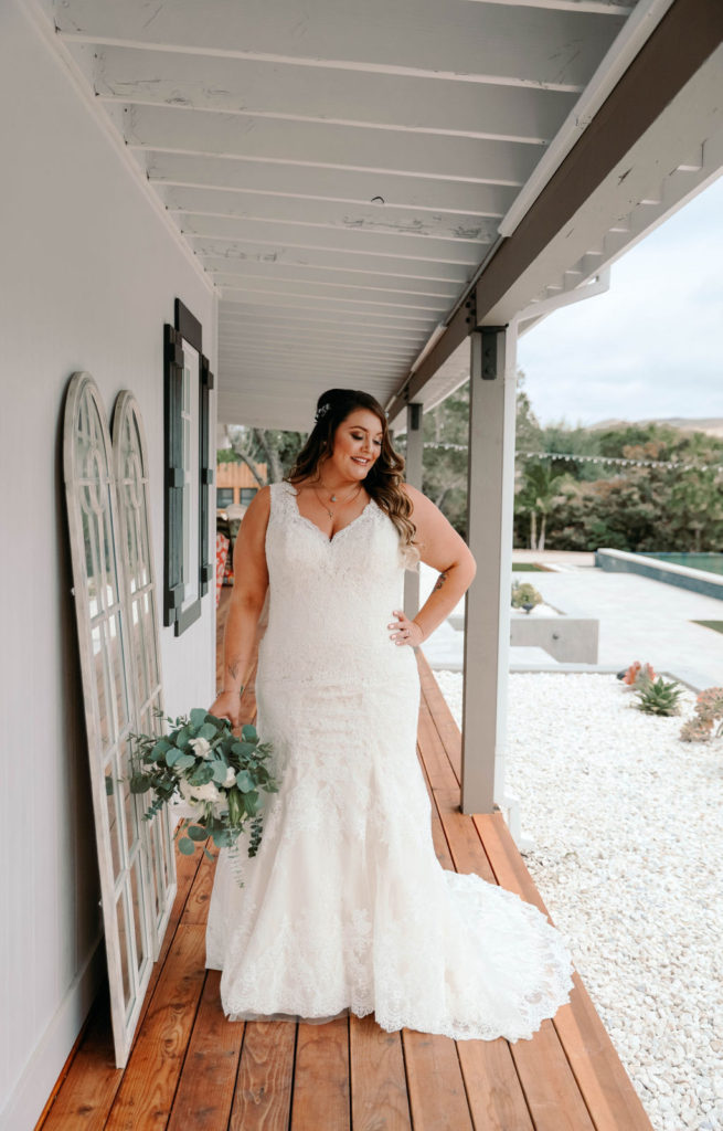 plus size bride wearing a vneck lace wedding dress and showing off her curves