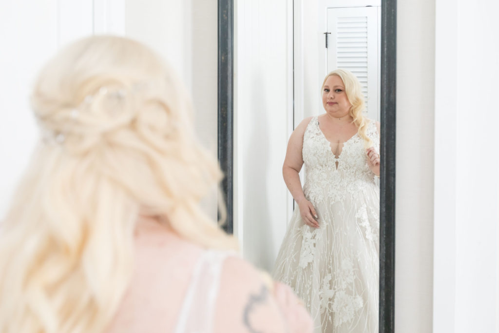 bright and airy bridal portrait of curvy bride looking into a mirror