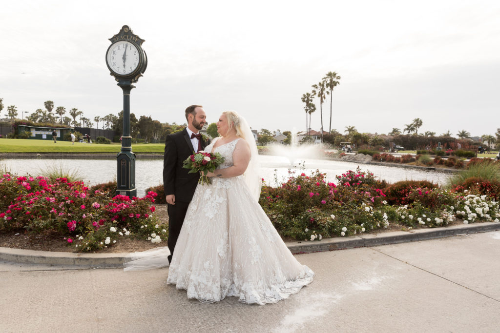wedding portrait by lake with fountain and flowers in the background