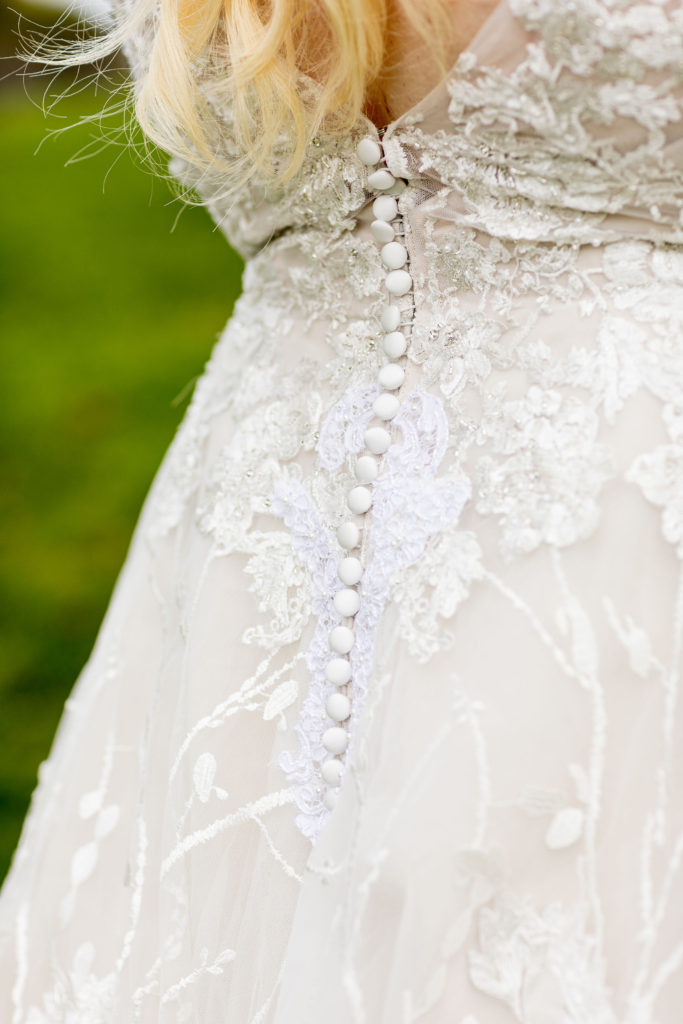 Close up of Shannon's deep v illusion back with buttons and textured lace detail on her ornate wedding dress.