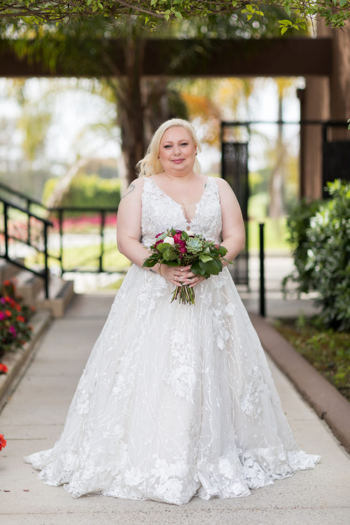 plus size bride with unique, ornate textured wedding gown with large floral lace appliques