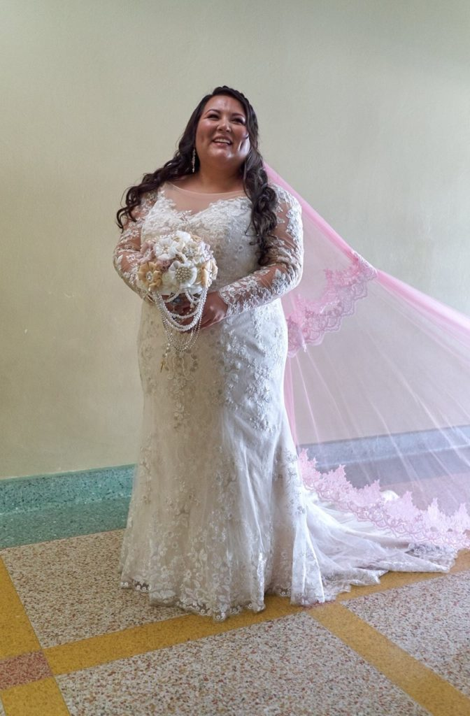 plus size bride with custom pink lace edge veil and brooch bouquet