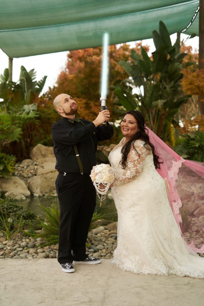 plus size bride in long sleeve lace wedding dress and groom in suit carrying a star wars light sabre