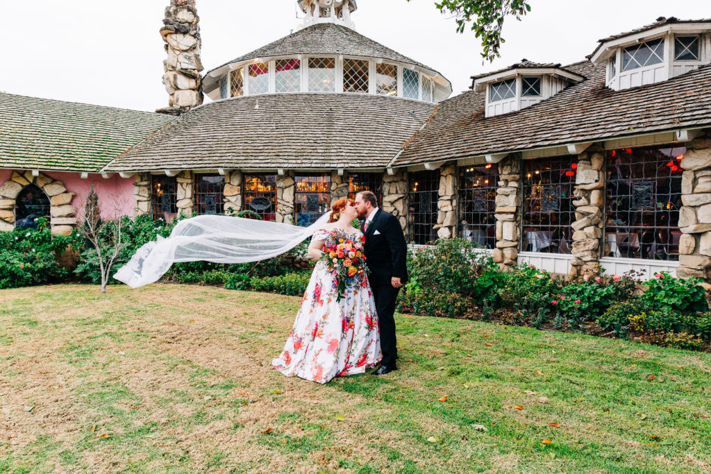 bride-wearing-floral-wedding-dress-and-groom-kissing-madonna-inn-california