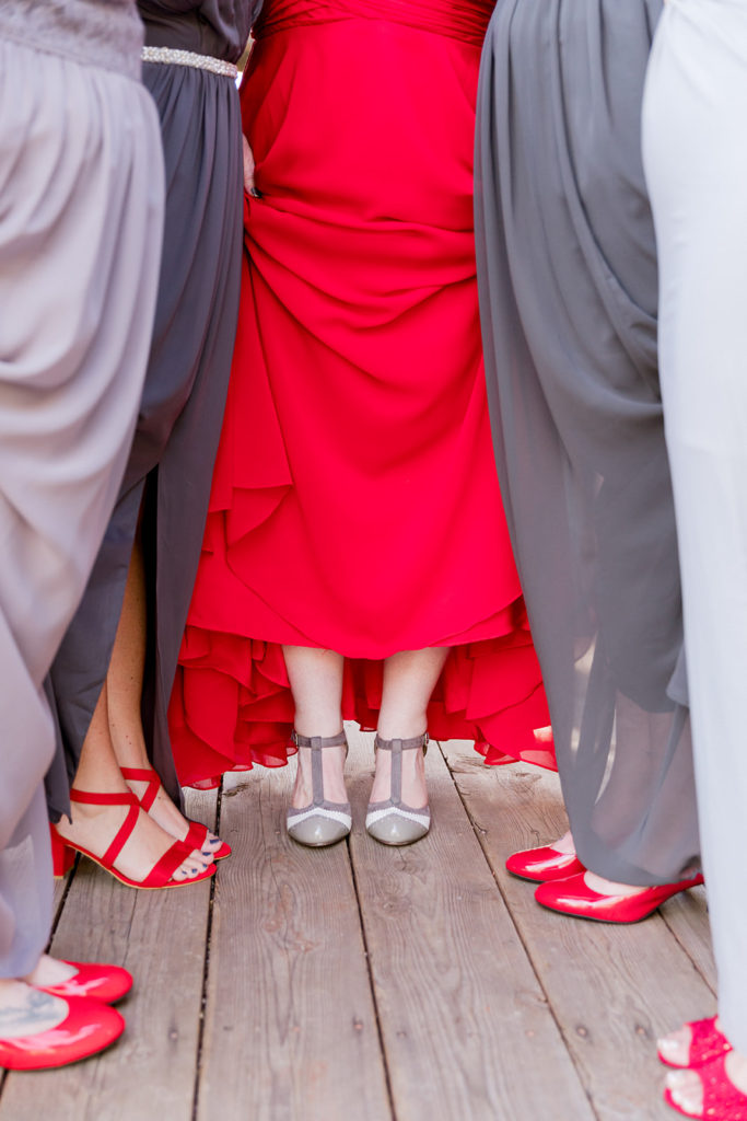 bridesmaids wearing red shoes and gray dresses with bride in custom red wedding dress