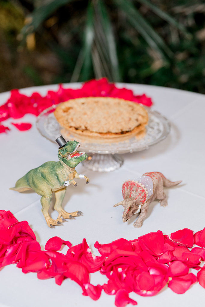 wedding dessert table with dinosaurs and red rose petals
