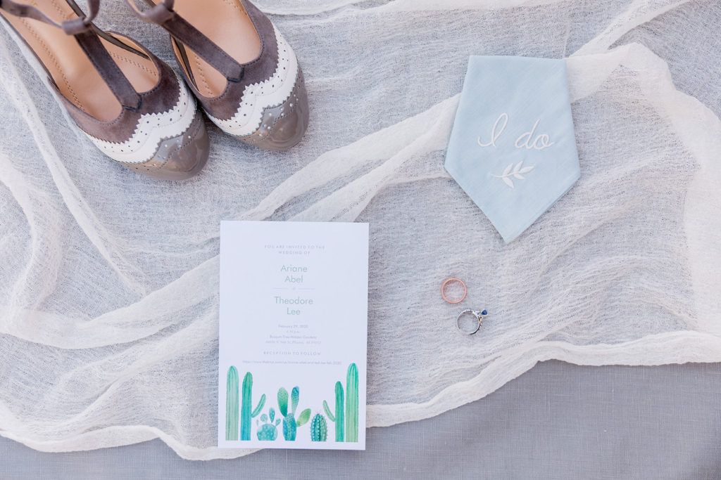 flatlay image of wedding shoes invitation rings and handkerchief