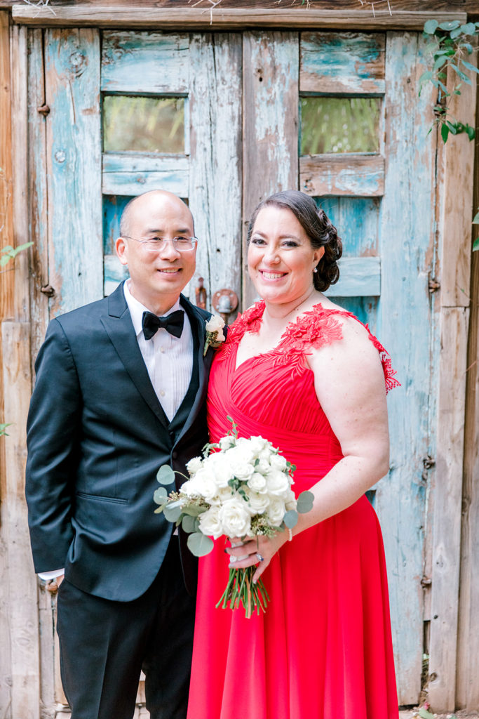 newlyweds wearing tux and custom red wedding dress