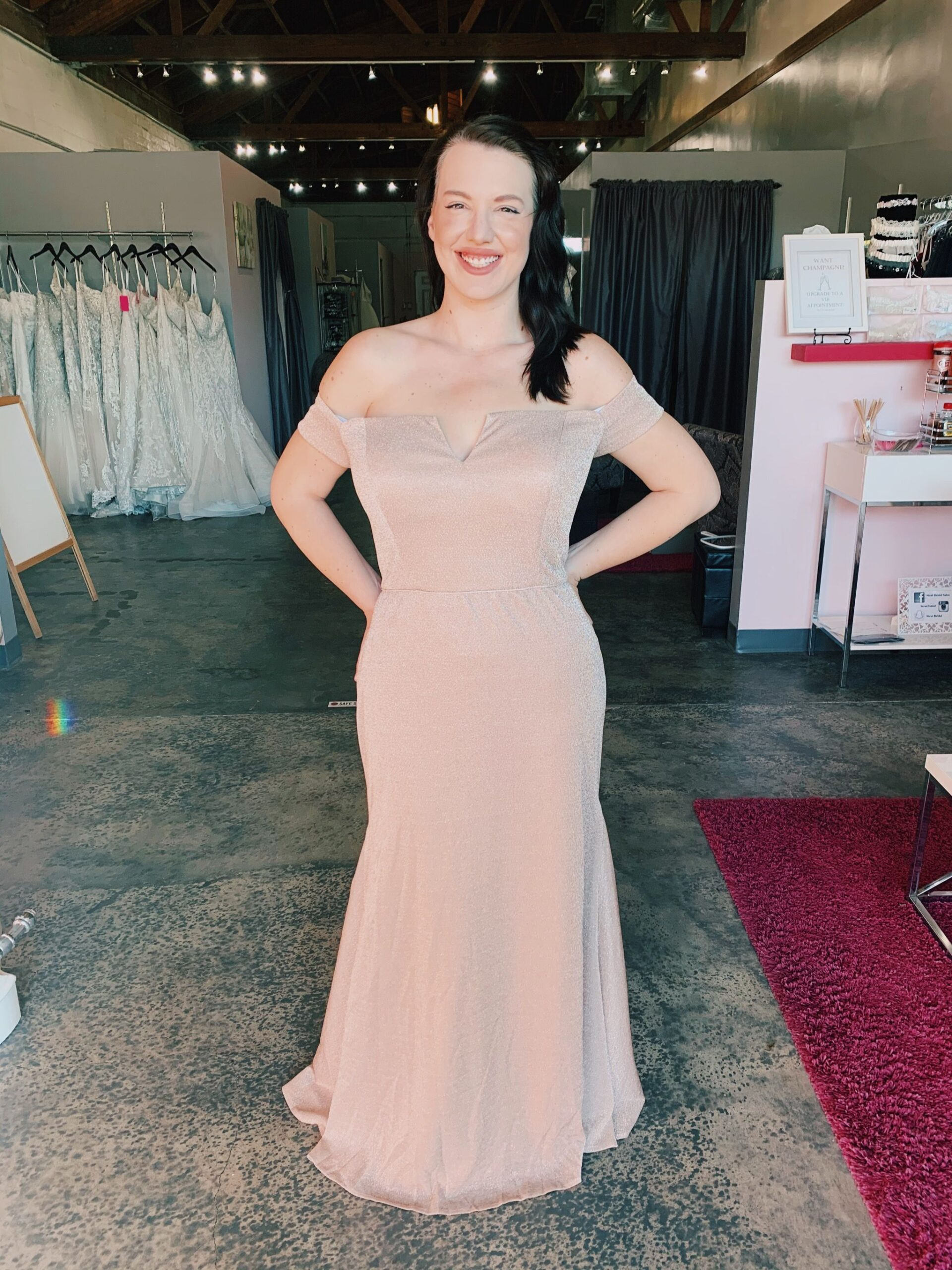 Smiling model in sparkly light pink bridesmaids dress off the shoulder sleeve