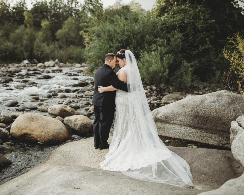 Beautiful couple on wedding day standing on rocks in waterfall in lace wedding dress and black tux