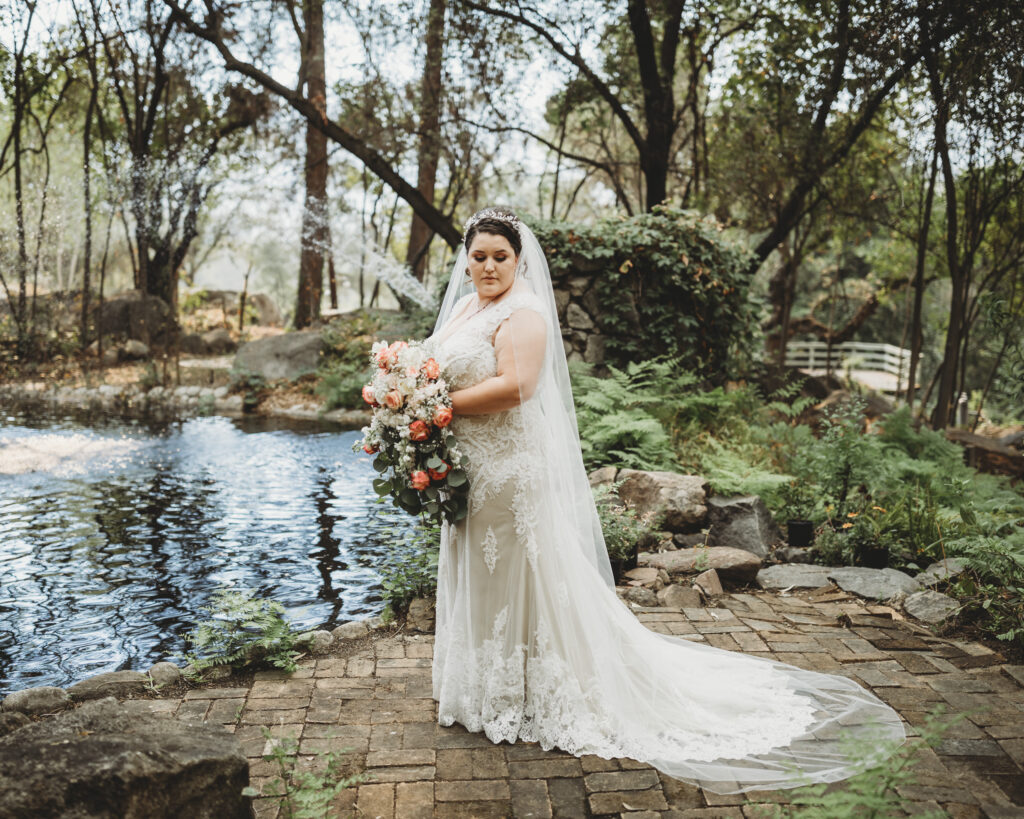 Beautiful plus sixe bride in lace dress with white and coral flowers long veil by waterfall and lake
